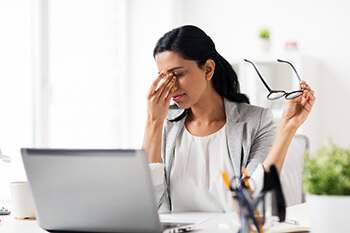 Woman suffering from Dry Eyes in the office