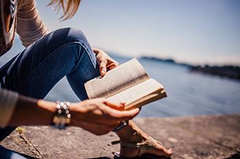 Woman reading a book next to a lake