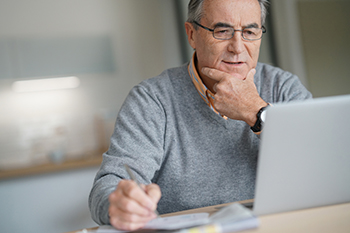 Older man reading a laptop
