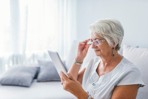 Older Woman with Glasses Attempting to Read
