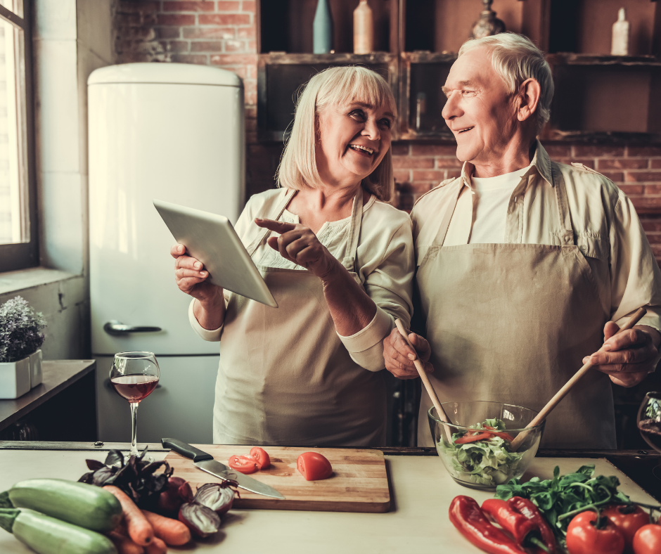 older couple cooking and laughing
